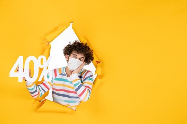 Vooraanzicht jonge man in masker met schrijven op geel gezondheidsvirus pandemie winkelen covid-foto verkoop kleur