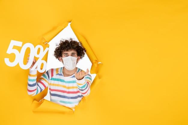 Vooraanzicht jonge man in masker met schrijven op geel virus winkelen gezondheid covid foto's verkoop kleur pandemie