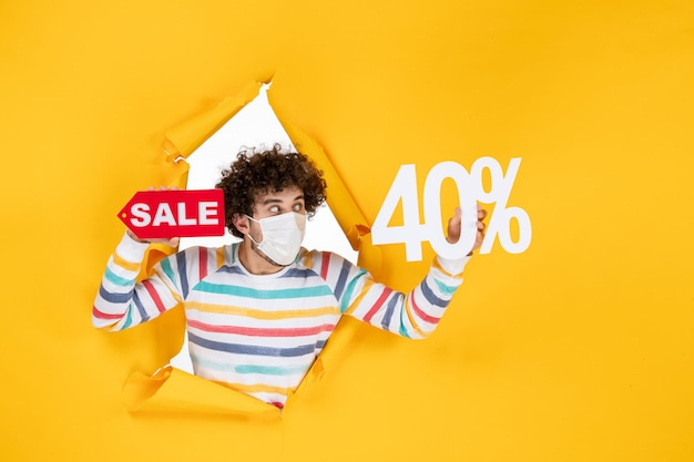 Vooraanzicht jonge man in masker met schrijven op gele gezondheidspandemie winkelen covid-virus fotokleur