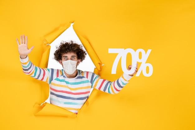 Vooraanzicht jonge man in masker met schrijven op gele kleur virus covid-foto's winkelen