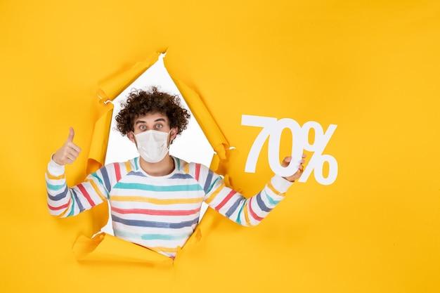 Vooraanzicht jonge man in masker met schrijven op gele verkoop kleur virus covid-foto's winkelen