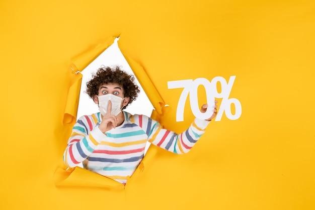 Vooraanzicht jonge man in masker met schrijven op gele verkoopkleuren virus covid-foto's winkelen