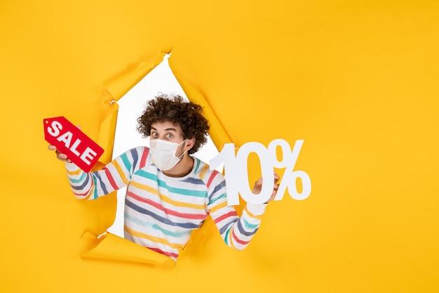 Vooraanzicht jonge man in masker vasthouden en verkopen schrijven op gele foto gezondheid covid- coronavirus pandemische verkoop kleur