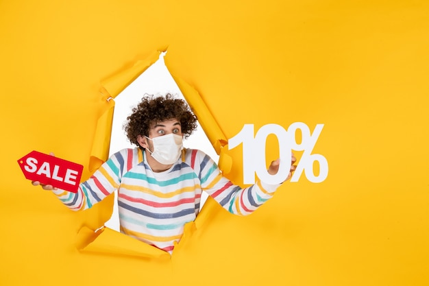 Vooraanzicht jonge man in masker vasthouden en verkopen schrijven op gele foto gezondheid covid pandemische verkoop kleur