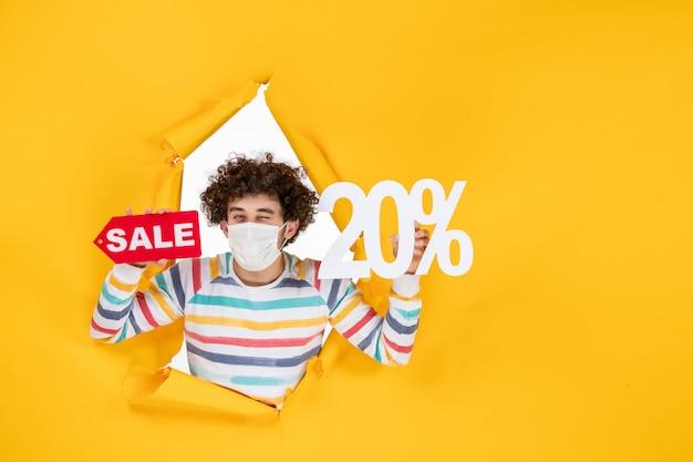 Vooraanzicht jonge man in masker vasthouden en verkopen schrijven op gele kleur verkoop coronavirus gezondheid covid- foto pandemie