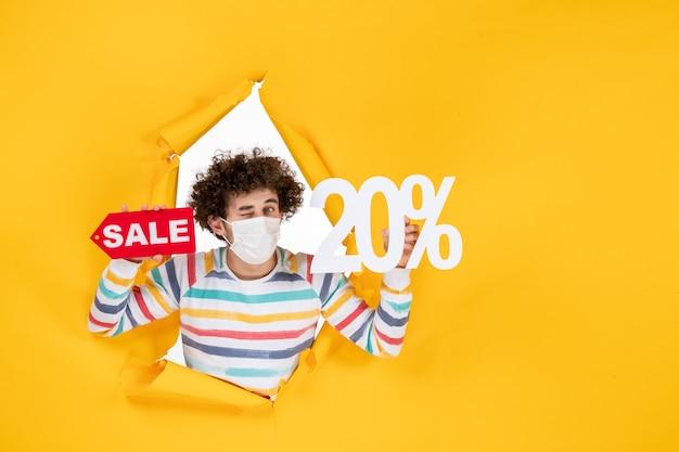 Vooraanzicht jonge man in masker vasthouden en verkopen schrijven op gele kleur winkelen coronavirus gezondheid covid- foto pandemie