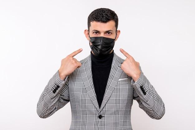 Vooraanzicht jonge man in pak wijzend op masker staande op witte geïsoleerde achtergrond