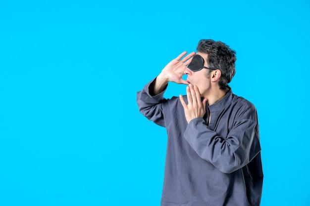 Vooraanzicht jonge man in pyjama en slaapverband op blauwe achtergrond donkere rust nachtmerrie slaap slaapkamer droom nacht kleur