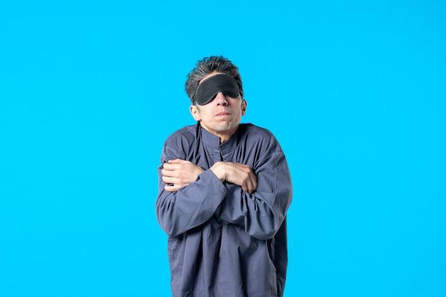 Vooraanzicht jonge man in pyjama en slaapverband rillend op blauwe achtergrond slaap droom nacht kleur nachtmerrie donker rust slaapkamer bed