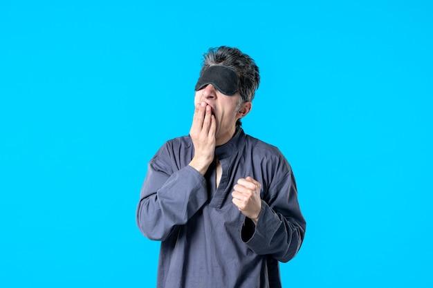 Vooraanzicht jonge man in pyjama en slapend verband geeuwen op blauwe achtergrond kleur rust nacht nachtmerrie bed slaap donker slaapkamer droom