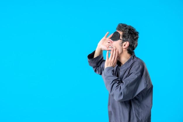Vooraanzicht jonge man in pyjama en verband om te slapen op blauwe achtergrond donkere kleur rust nachtmerrie slaap bed nacht droom