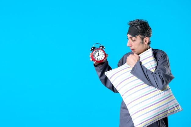 Vooraanzicht jonge man in pyjama met kussen en klokken op blauwe achtergrond donkere nachtmerrie slaapkamer slapeloosheid nacht bed laat slaap rust droom