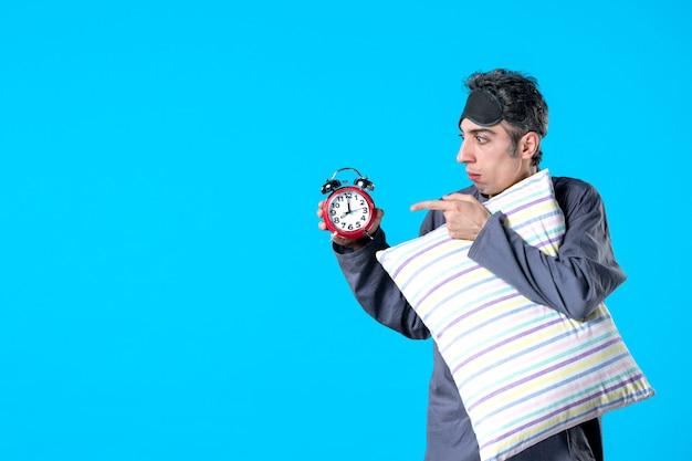 Vooraanzicht jonge man in pyjama met kussen en klokken op blauwe achtergrond nachtmerrie droom slaapkamer slapeloosheid rust donkere nacht bed laat