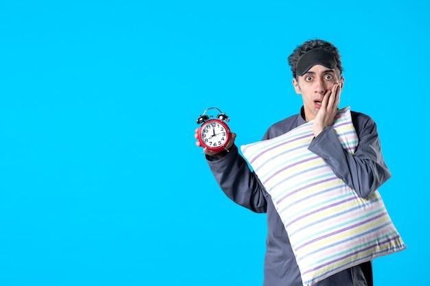 Vooraanzicht jonge man in pyjama met kussen en klokken op blauwe achtergrond nachtmerrie droom slaapkamer slapeloosheid slaap rust donkere nacht bed laat Premium Foto