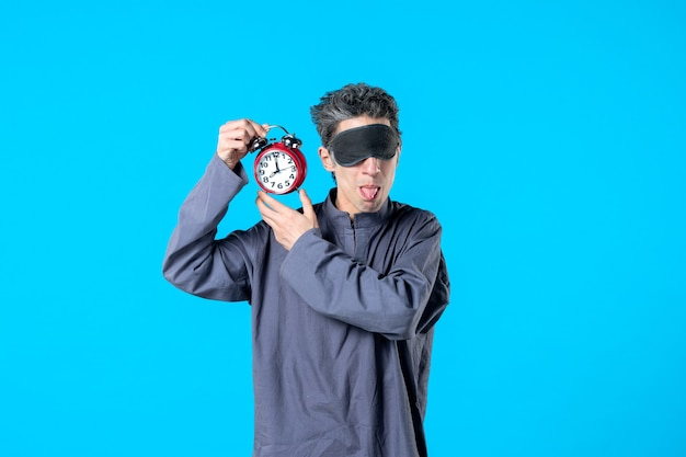 Vooraanzicht jonge man in pyjama met rode klokken op blauwe achtergrond donkere nachtmerrie slapeloosheid bed kleur slaap laat droom