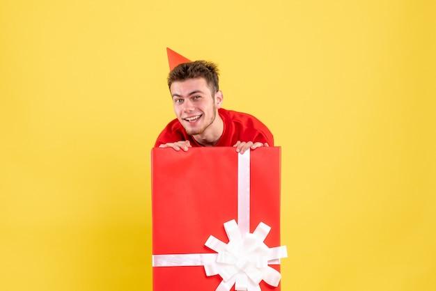Vooraanzicht jonge man in rood shirt in huidige doos glimlachen
