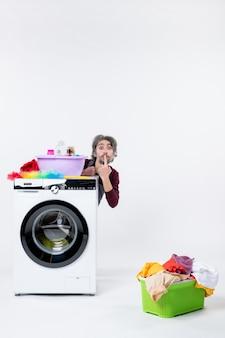 Vooraanzicht jonge man in schort die achter de wasmachine zit en een stil teken maakt op de witte muur