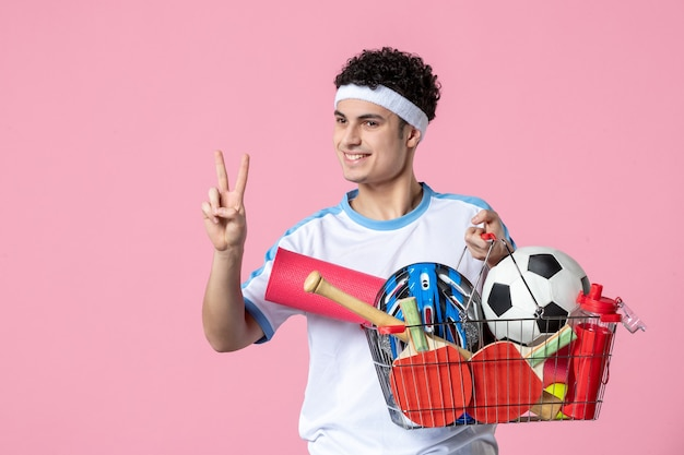 Vooraanzicht jonge man in sportkleding met mand vol met sport dingen roze muur