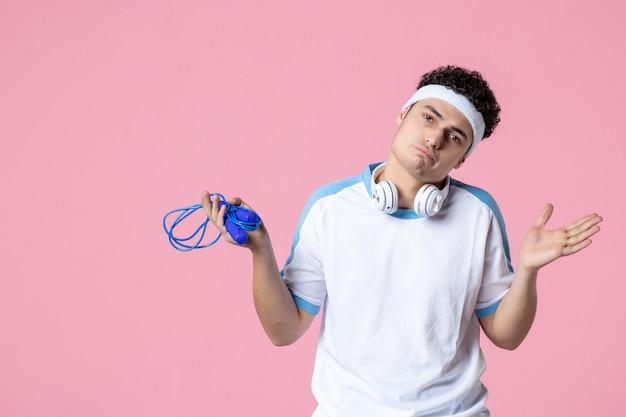 Vooraanzicht jonge man in sportkleding met springtouw op de roze muur