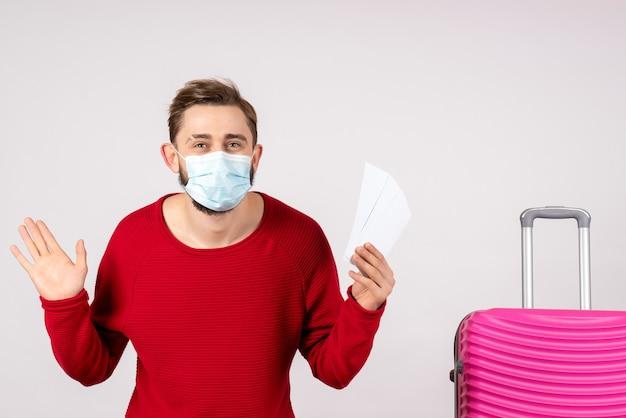 Vooraanzicht jonge man in steriel masker met kaartjes op witte muur covid-vliegtuig vakantie emotie virus vlucht reis