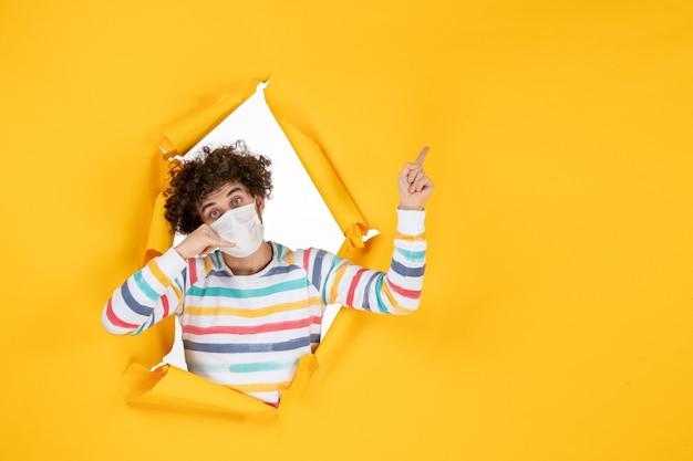 Vooraanzicht jonge man in steriel masker op gele gezondheid covid coronavirus menselijke foto pandemische kleur