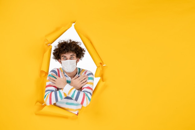 Vooraanzicht jonge man in steriel masker op gele gezondheidskleurenfoto covid-pandemie virus mens