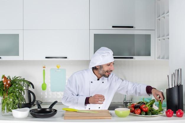 Vooraanzicht jonge man in uniform die groenten van tafel haalt