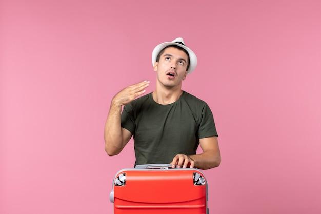 Vooraanzicht jonge man in vakantie die lijdt aan hitte op roze ruimte