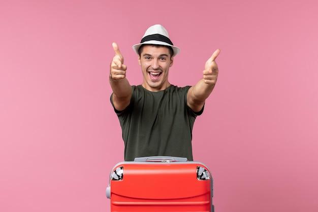 Vooraanzicht jonge man in vakantie die zich gelukkig voelt op roze ruimte