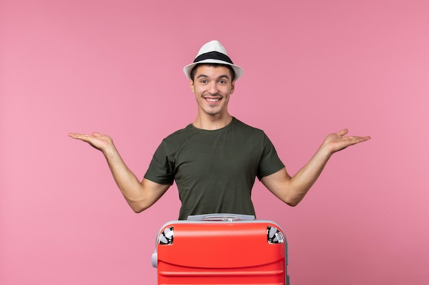 Vooraanzicht jonge man in vakantie met grote tas en glimlach op roze ruimte