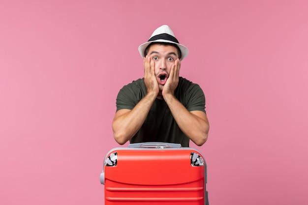 Vooraanzicht jonge man in vakantie met grote zak en verbaasde uitdrukking op roze ruimte