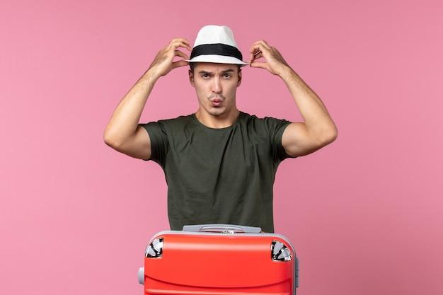 Vooraanzicht jonge man in vakantie met hoed op de roze ruimte