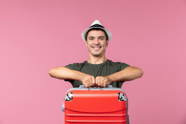 Vooraanzicht jonge man in vakantie met rode tas op roze ruimte carrying