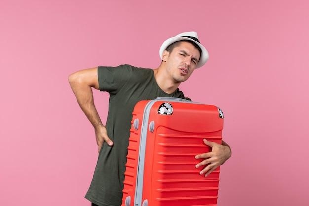 Vooraanzicht jonge man in vakantie met zijn grote tas en lijdend aan pijn op roze ruimte