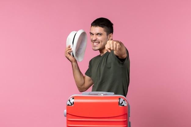 Vooraanzicht jonge man in vakantie met zijn hoed met zijn vuist op roze ruimte pink