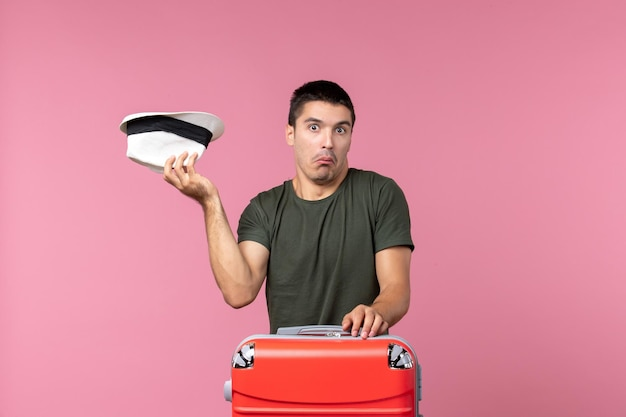 Vooraanzicht jonge man in vakantie met zijn hoed op lichtroze ruimte