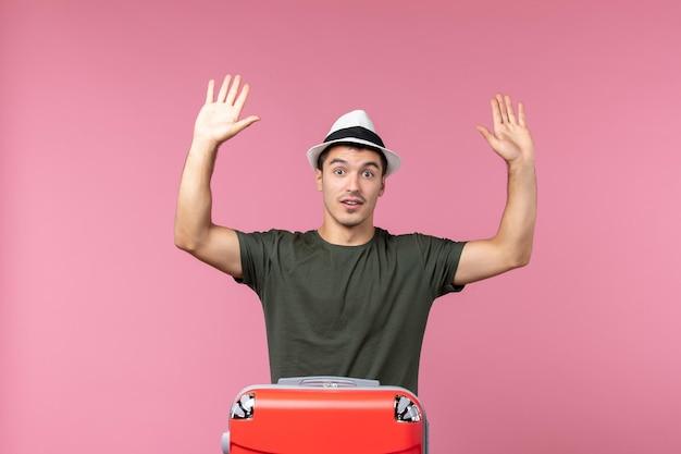 Vooraanzicht jonge man in vakantie met zijn rode tas op lichtroze ruimte