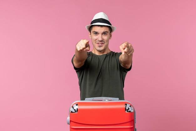 Vooraanzicht jonge man in vakantie wijzend op roze ruimte