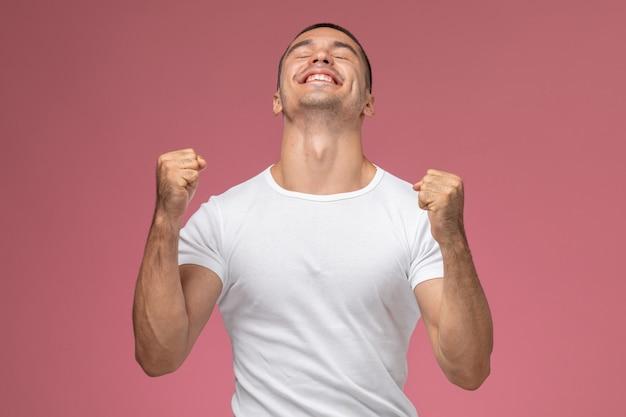 Vooraanzicht jonge man in wit overhemd emotioneel vreugde op de roze achtergrond