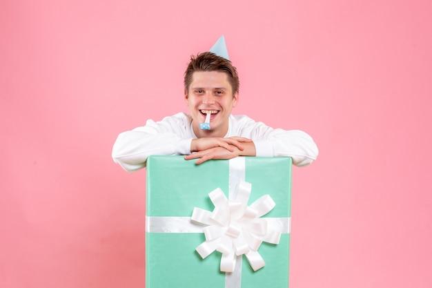 Vooraanzicht jonge man in wit overhemd met pet en heden lachen op roze achtergrond