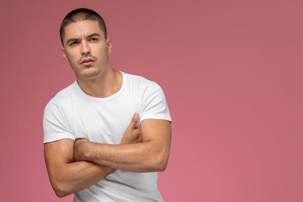 Vooraanzicht jonge man in wit overhemd poseren gewoon op de roze achtergrond