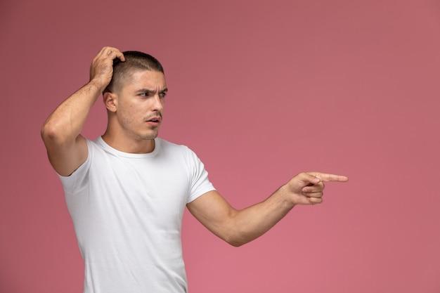 Vooraanzicht jonge man in wit overhemd poseren met verwarde uitdrukking op de roze achtergrond