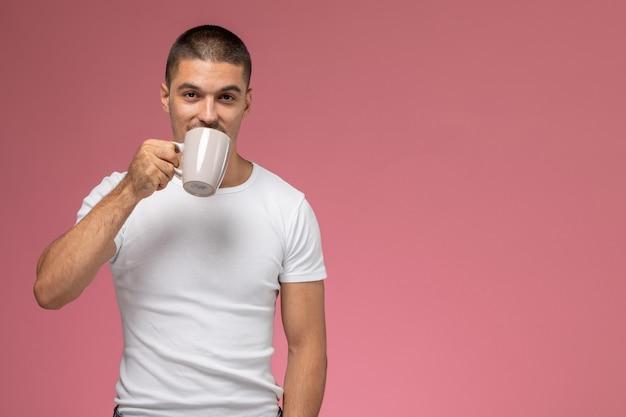 Vooraanzicht jonge man in wit t-shirt koffie drinken op roze achtergrond