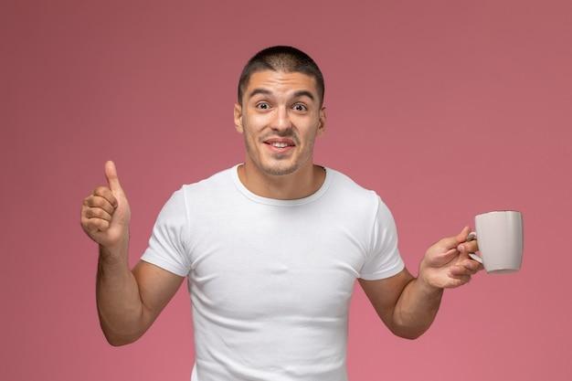 Vooraanzicht jonge man in wit t-shirt kopje koffie op de roze achtergrond te houden