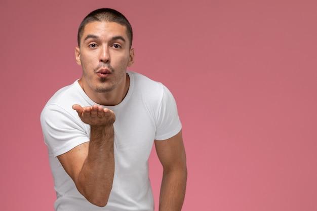 Vooraanzicht jonge man in wit t-shirt lucht kussen verzenden op roze achtergrond