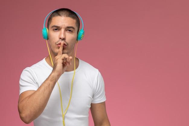 Vooraanzicht jonge man in wit t-shirt luisteren naar muziek stilte teken op lichtroze achtergrond tonen