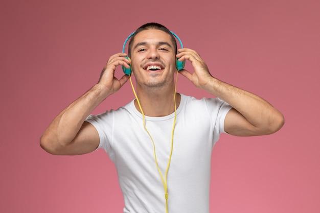 Vooraanzicht jonge man in wit t-shirt luisteren naar muziek via oortelefoons met glimlach op roze achtergrond