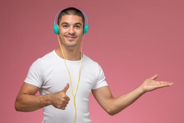 Vooraanzicht jonge man in wit t-shirt luisteren naar muziek via zijn koptelefoon lachend op lichtroze achtergrond