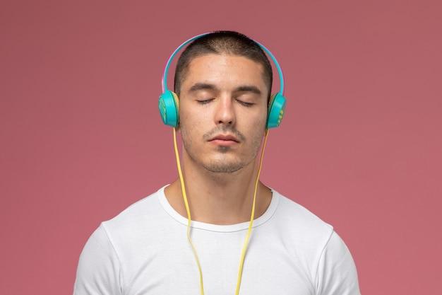 Vooraanzicht jonge man in wit t-shirt luisteren naar muziek via zijn koptelefoon op de roze achtergrond