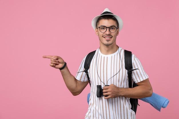 Vooraanzicht jonge man in wit t-shirt met verrekijker op de roze achtergrond